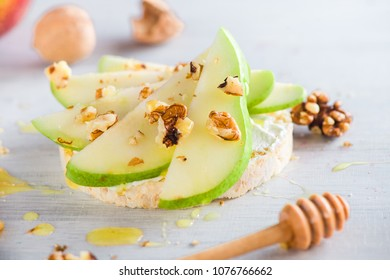 Easy crisp bread snack with pear slices, creamy cheese, honey and walnuts. Diet breakfast recipe in high key with copy space.
