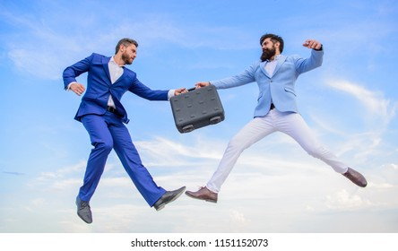 Easy deal business. Businessmen jump fly mid air while hold briefcase. Case with raise your business. Successful transaction between businessmen. Briefcase handover in heaven blue sky background.