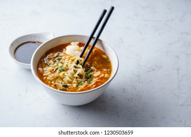 Easy japanese ramen with noodles, pork broth, egg and leek in white bowl on concrete background with copy space