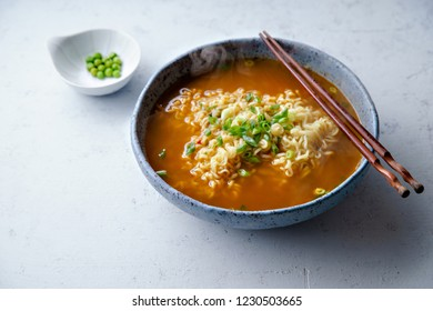 Easy japanese ramen with noodles, pork broth, egg and leek in handmade blue ceramic bowl with wooden chopsticks. Concrete background