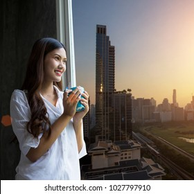 Easy lifestyle Asian woman waking up in the morning taking some relaxing in the city hotel room