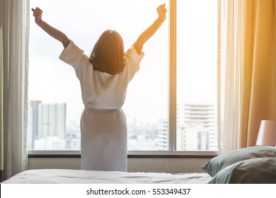 Easy lifestyle Asian woman waking up in weekend morning taking some rest relaxing in comfort city hotel room enjoying world lazy day, having happy life quality balance concept