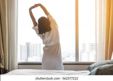 Easy lifestyle Asian woman waking up in the morning lazily taking some rest relaxing in hotel room