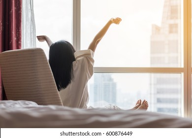 Easy lifestyle Asian woman waking up in the morning taking some rest relaxing in hotel room