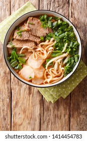 Easy Recipe forLanzhou Beef Noodle Soup closeup in a bowl on the table. Vertical top view from above