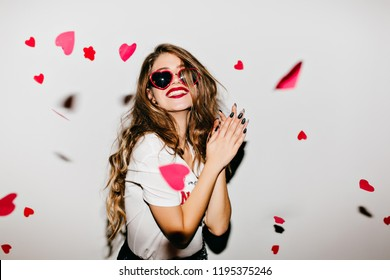 Easy-going girl with long hair expressing positive emotions in valentine's day. Excited lady looking at fallen paper hearts and laughing.