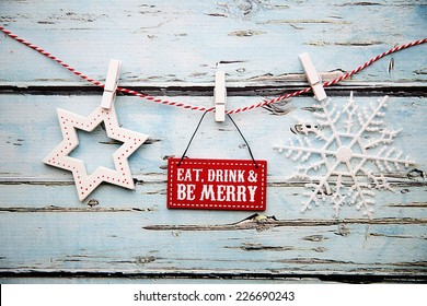 """""""Eat, drink and be merry"""" sign against a distressed wooden background"""