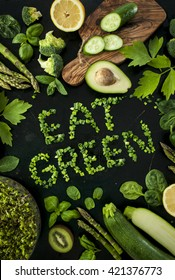 eat green - healthy diet concept. Variety of green vegetables and some fruits on the black board background with natural chive lettering