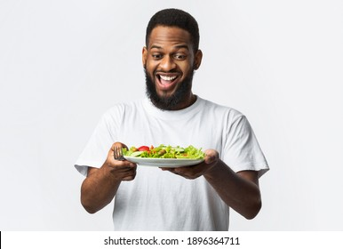 Eat Healthy. Excited African Bearded Guy Holding Salad Looking At Fresh Vegetables On Plate Standing Over White Studio Background. Dieting, Male Nutrition And Weight Loss