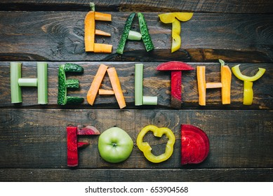 Eat healthy food fresh vegetables flat lay lettering on dark wooden table top view. Nutrition organic meal ingredients concept. Nice cooking postcard, poster, banner.