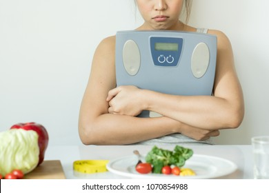 Eat less and eat healthy. Depressed girl holding weight scales and look at vegetables in plate her bored healthy breakfast.