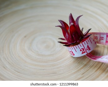 eat less live longer concept by measuring tape holding fresh Rosella flower on copy space