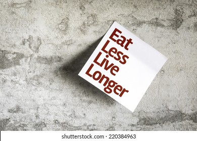 Eat Less Live Longer on Paper Note with texture background