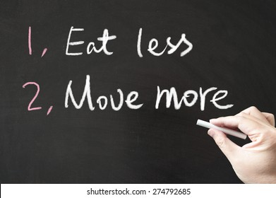 Eat less and move more words written on the blackboard using chalk