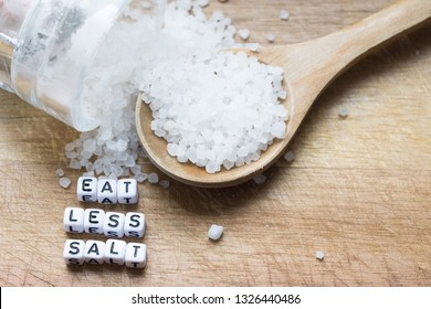 Eat less salt advice written with plastic letter beads on wooden cutting board, near granulated salt – healthy food lifestyle