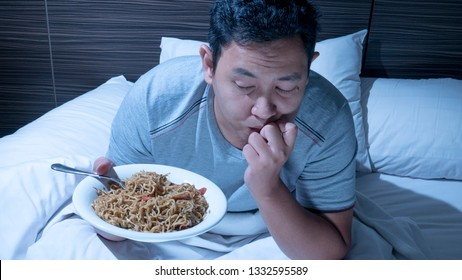 Eat at midnight, bad eating habit, late night dinner on bed, Asian man eat noodle