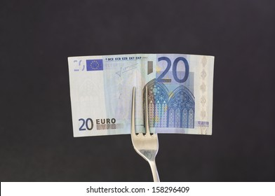 Eat money / Twenty euro note in the fork ready to be eaten