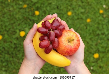 Eat more fruits: hands holding grapes, an apple and a banana, grass background with dandelions