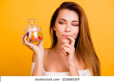Eat or not eat?! Pretty, minded girl pondering, holding little colorful choco in clear bank, touching her lips, mouth with finger, looking at candies in jar, standing over yellow background