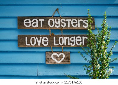 Eat oysters love longer funny handmade sign at an Australia oyster farm sheed