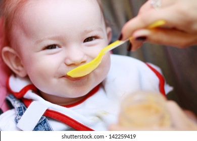 Eat smeared pretty baby girl eating from spoon outdoor