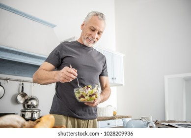 Eat vitamins. Cheerful pensioner being in the kitchen and keeping smile on his face while mixing salad