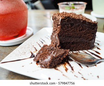 eaten chocolate cake with chocolate sauce on white plate and  Strawberry juice blended