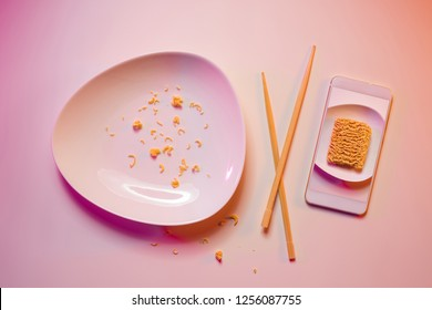 Eaten meal documented on smartphone. Crumbs on the plate, chopsticks and mobile phone captured from above (top view). Colorful light - pink and orange tonal transitions.
