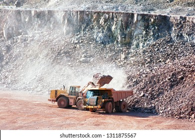 eath mover loading stones on a dumper truck. mining indrusties.