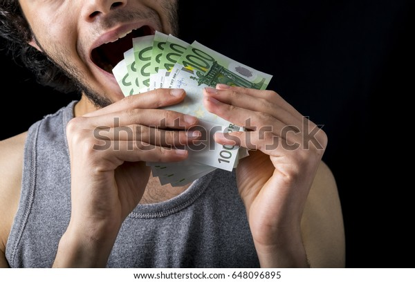 eating 100 euro money, hand holding one hundred euro cash isolated on a black background
