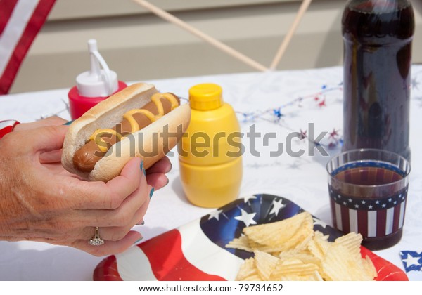 Eating a 4th Of July hotdog with mustard