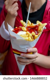 Eating of Belgian fried potatos chips with ketchup and mayonnaise, street fast food, unhealthy food