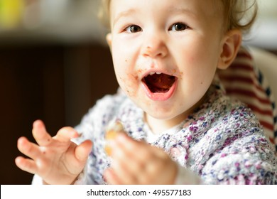 Eating cheerful baby girl with messy face. The one-year-old child eats and laughs. Happy toddler eats and screams with delight. Portrait of a toddler eating sweets.