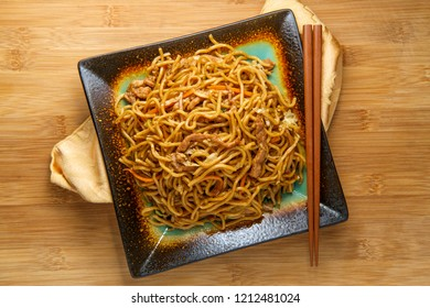 Eating Chinese pork lo mein noodles with chopsticks