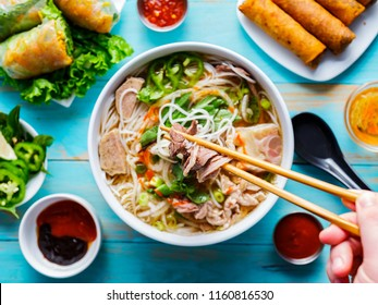 eating colorful Vietnamese pho bo with selective focus on chopsticks from top down view