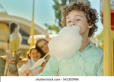 Eating the cotton candy is a real pleasure for readhead boy with closed eyes. Two happy sisters in the background embrace each other.