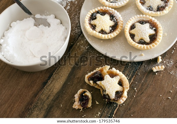 Eating delicious freshly baked Christmas mince pies decorated with pastry stars and sprinkled with icing sugar, one half eaten pie with crumbs in the foreground