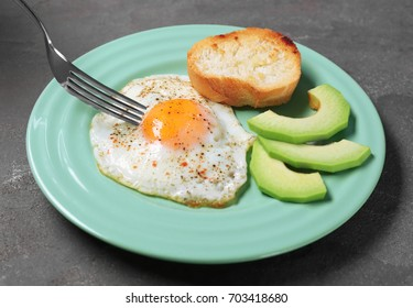 Eating delicious over easy egg with toast and avocado slices on kitchen table