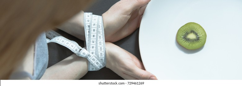 Eating disorder, bulimia and anorexia concept, female hands tided up with a measure tape holding a plate with fruit