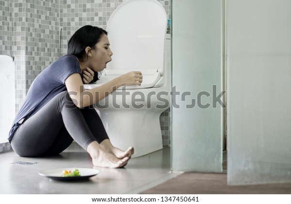 Eating disorder concept. Young woman vomiting after eating a plate of salad in the bathroom