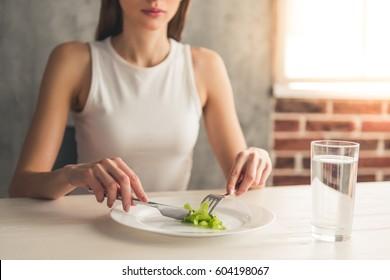 Eating disorder. Cropped image of girl eating lettuce