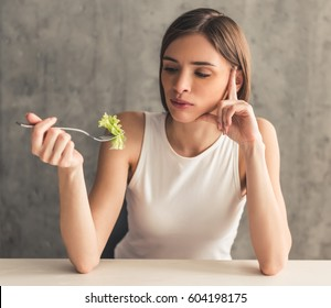 Eating disorder. Girl is holding a fork with lettuce and looking at it
