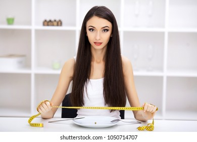 Eating disorder. Girl is holding a plate and trying to put a pea on the fork