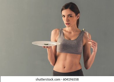 Eating disorder. Girl is holding a plate with a slice of cucumber on it, isolated on white