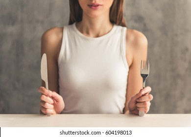 Eating disorder. Girl is sitting in front of an empty plate and holding a fork and a knife