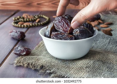 Eating dried dates. Almonds on wooden table. Traditional arabic food. Ramadan event.