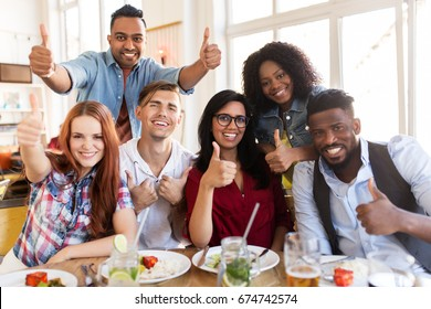 eating, food and people concept - group of happy international friends showing thumbs up gesture at restaurant table
