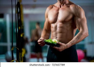 Eating food salad bodybuilding bodybuilder fitness gym body builder building muscles young man studio