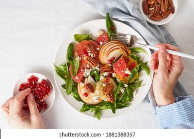 Eating fruits citrus salad with nuts, green lettuce. Balanced food. Top view of woman hands with plate of meal of Spinach with orange, grapefruit, apples, pecans
