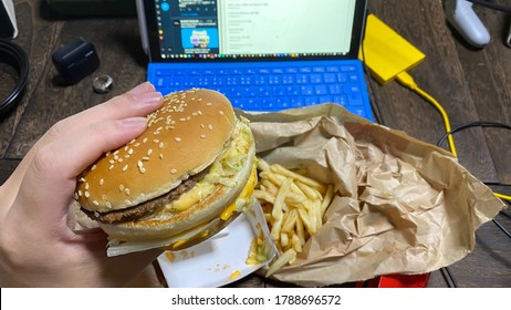 Eating hamburger and fried potatoes on the desk. Life style of Remote working and Working from home